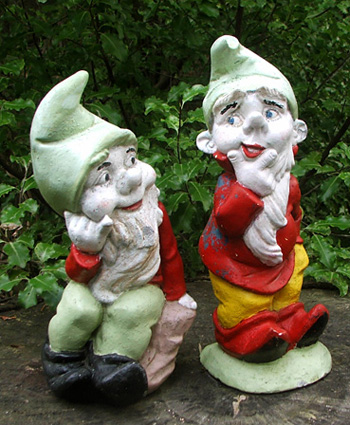 Two cheeky gnome chaps atop a tree stump